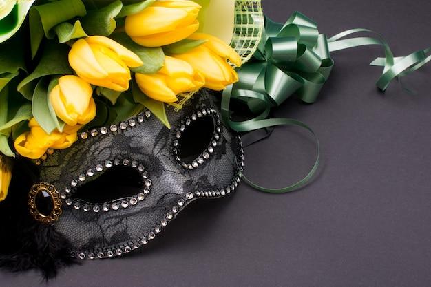 Carnaval masker met een boeket gele tulpen.