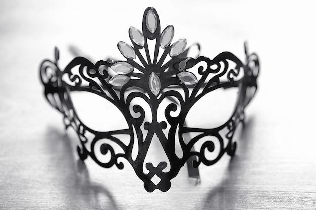 Carnaval masker op tafel. het onderwerp van camouflage op date tijdens een carnaval. venetiaans masker op een houten tafel in zwart-wit.