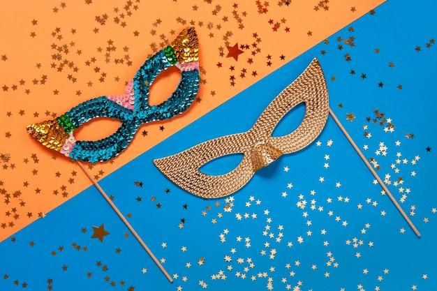 Carnaval maskerade maskers en gouden glitter confetti. bovenaanzicht, close-up op blauwe en oranje kleuren achtergrond
