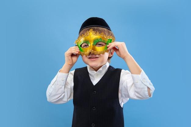 Carnavalsmasker proberen. portret van een jonge orthodoxe joodse jongen geïsoleerd op blauwe muur.