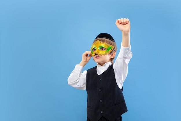 Carnavalsmasker proberen. portret van een jonge orthodoxe joodse jongen geïsoleerd op blauwe studio muur.