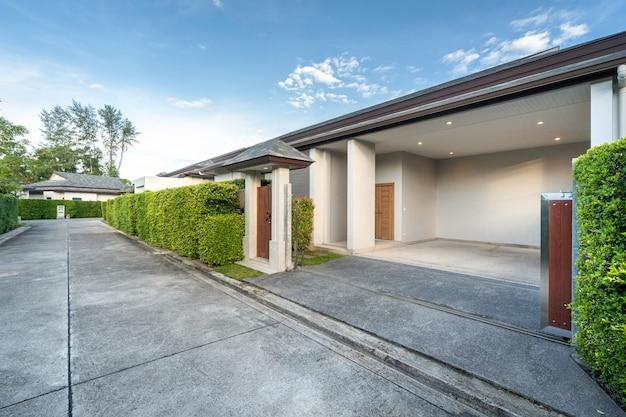 Carport van luxe villa met zwembad en kleine houten poort