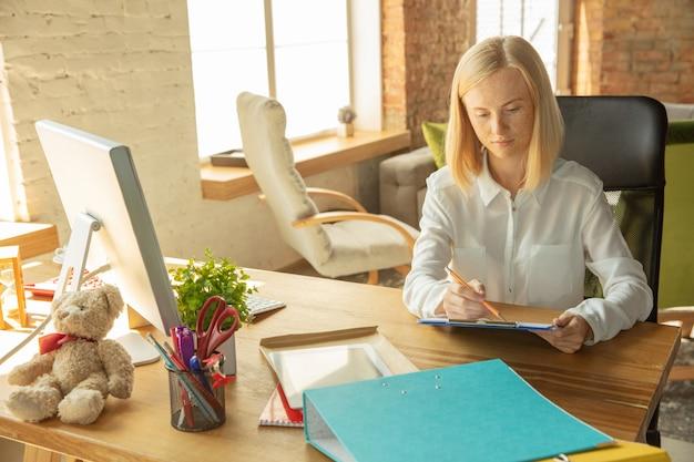 Carrière. een jonge zakenvrouw die zich op kantoor beweegt en een nieuwe werkplek krijgt. jonge vrouwelijke beambte in haar nieuwe kabinet die de zaken neemt. ziet er zelfverzekerd uit. business, lifestyle, nieuw levensconcept.