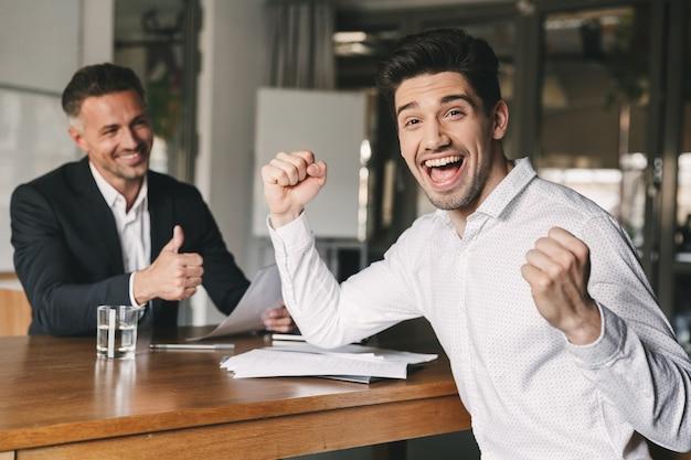 Carrière-, kantoor- en plaatsingsconcept - opgewonden blanke man 30s verheugend en balde vuisten na sollicitatiegesprek, sinds hij werd ingehuurd voor een baan in een groot bedrijf