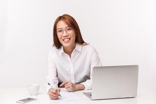 Carrière, werk en vrouwelijke ondernemers concept. close-up portret vriendelijk ogende beleefde aziatische vrouw, officemanager ondertekening deal met klant, info opschrijven, zitten in de buurt van laptop, glimlachend