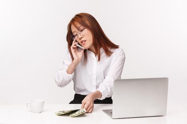 Carrière, werk en vrouwelijke ondernemers concept. close-upportret die van hardwerkende succesvolle aziatische onderneemster die op kantoor werken, dichtbij laptop zitten, geld tellen die oproepen op telefoon beantwoorden
