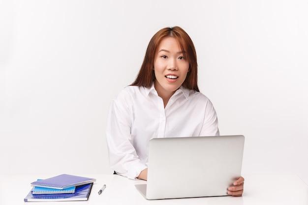 Carrière, werk en vrouwelijke ondernemers concept. close-upportret van vrij aziatische vrouwelijke bureaumanager die met laptop werken, bekijkend cliënt als het neerschrijven van info bij computer,