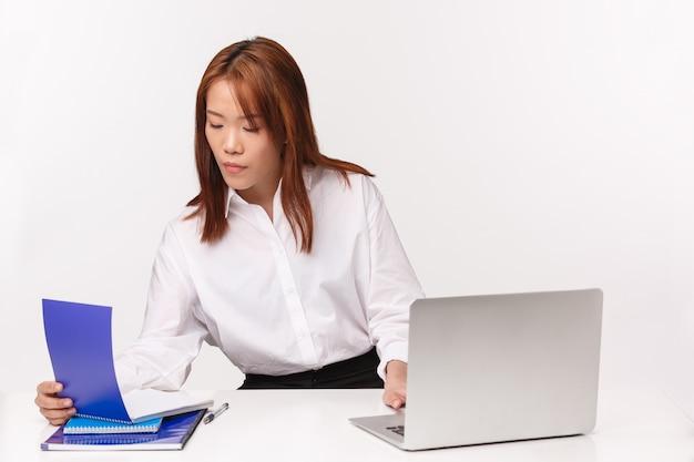 Carrière, werk en vrouwelijke ondernemers concept. het close-upportret van bezige ernstig ogende onderneemster in haar bureau, die nota's in notitieboekje controleren, info in laptop neerschrijven, gebruikt computer