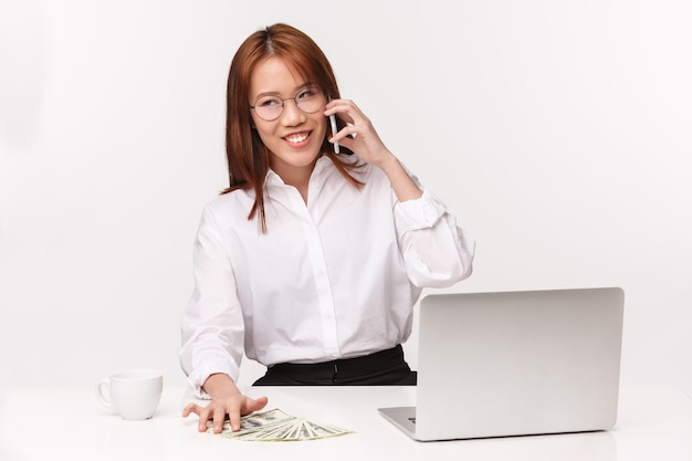 Carrière, werk en vrouwelijke ondernemers concept. het close-upportret van succesvolle jonge aziatische rijke onderneemster ondertekende goede overeenkomst, zittend bureau met laptop, geld, die op mobiele telefoon spreken