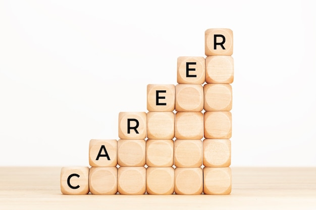 Carrièretekst op houten kubussen in de vorm van een opgaande trap op houten tafel en witte achtergrond