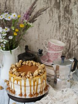 Carrot cake met gezouten karamel en cheesecake binnen, versierd met popcorn en karamel