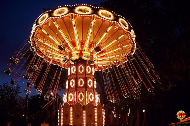 Carrousel draaimolen in pretpark bij nachtstad