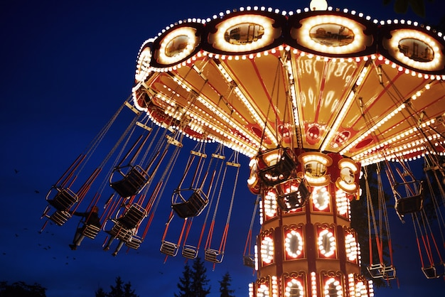 Carrousel draaimolen in pretpark in de nacht stad