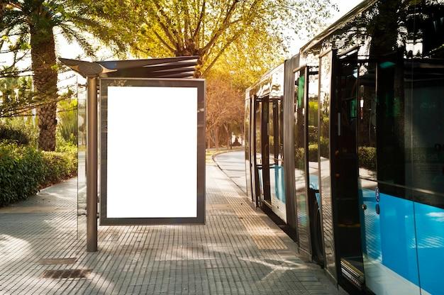 Cartelera vertical en blanco blanco en la parada de autobs en la calle de la ciudad