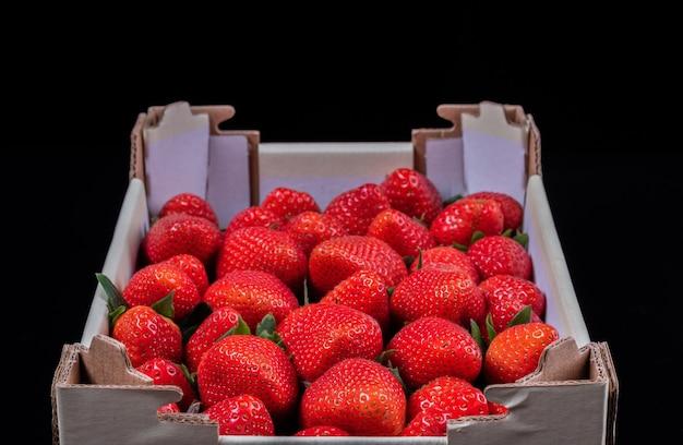 Cartoon doos met aardbeien op zwarte ondergrond. klaar voor het dessert.