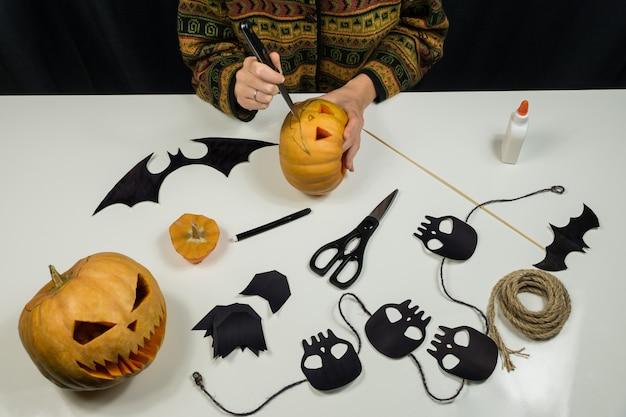 Carving een jack'o'lantern aan een tafel van bovenaanzicht