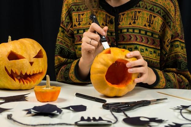 Carving pompoen voor jack'o'lantern gezicht. de vrouwelijke persoon bereidt decoratie voor halloween voor en maakt enge pompoengezichten bij een woonkamerlijst