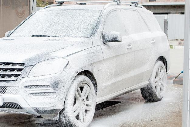 Carwash met schuim in wasstraat. carwash. wasmachine op het station. auto wassen concept. wagen in schuim