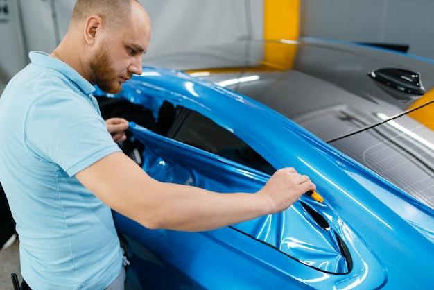 Carwrapping, monteur snijdt beschermende vinylfolie of film op voertuig. werknemer maakt automatische detaillering. autolakbeschermingscoating, professionele afstemming