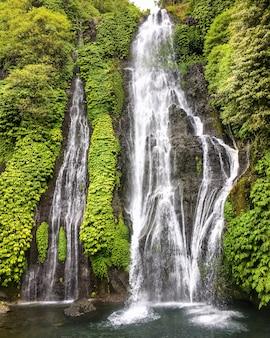 Cascade van de wildernis de hoge waterval in tropisch regenwoud met rots op bali, indonesië.