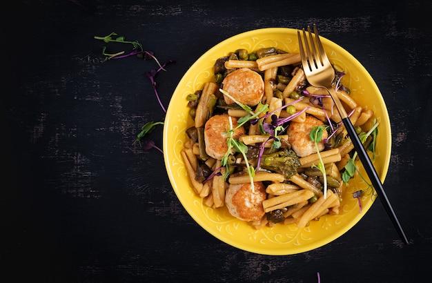 Caserecce pasta met gehaktballen in zoetzure saus en groenten in kom