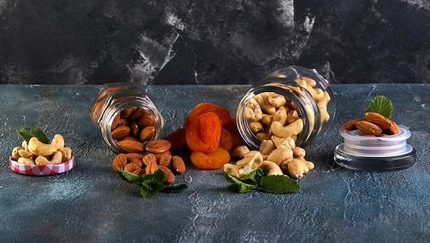 Cashew-amandelen spatten uit transparante blikjes, gedroogde abrikozen liggen ertussen