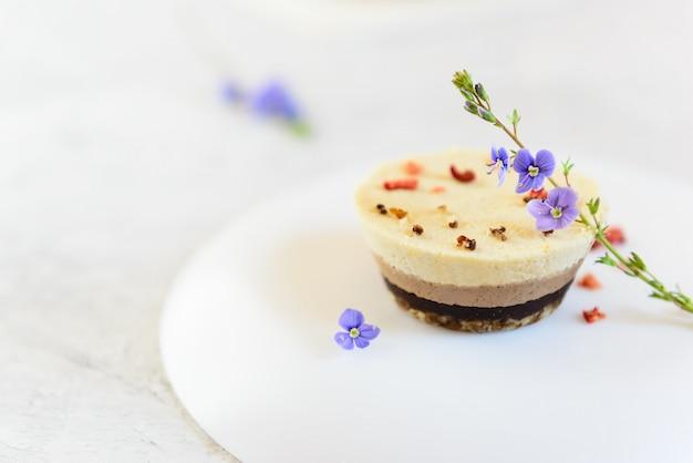 Cashew cake met chocolade, amandelen en kokos op een witte plaat