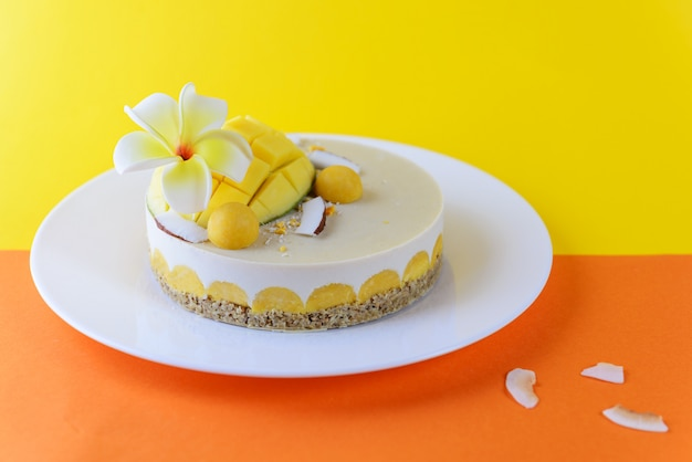 Cashew cake met mango praline en kokos, versierd met frangipanibloem. suiker, lactose, glutenvrij. gezond eten, veganistisch.