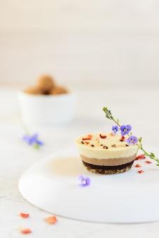 Cashew cake versierd met bloemen en gesublimeerde bessen