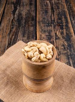 Cashew in een houten kop zijaanzicht op een stuk zak