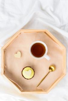 Cashewcake met een kopje thee op een dienblad op het bed.