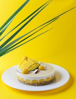 Cashewcake met mango en kokos en groene bladeren. suiker, lactose, glutenvrij.