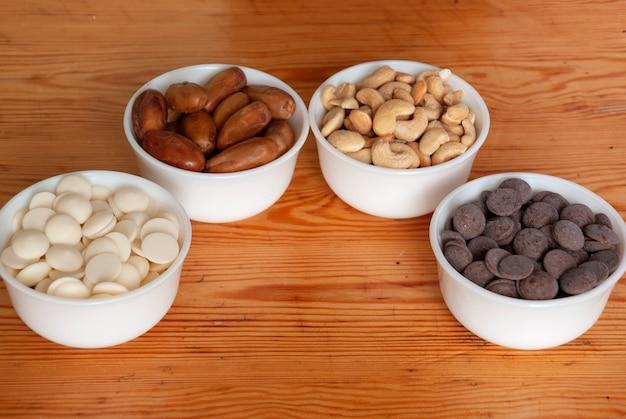 Cashewnoten, dadels, witte en melkchocolade druppels in witte kleine kommen close-up.