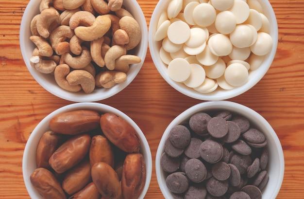 Cashewnoten, dadels, witte en melkchocolade druppels in witte kommen.