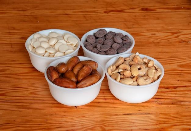 Cashewnoten, dadels, witte en melkchocolade druppels in witte kommetjes.