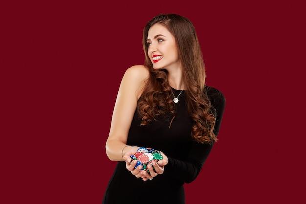 Casino, gokken, poker, mensen en entertainment concept - vrouw pokerspeler in zwarte jurk met chips in handen op rode achtergrond.
