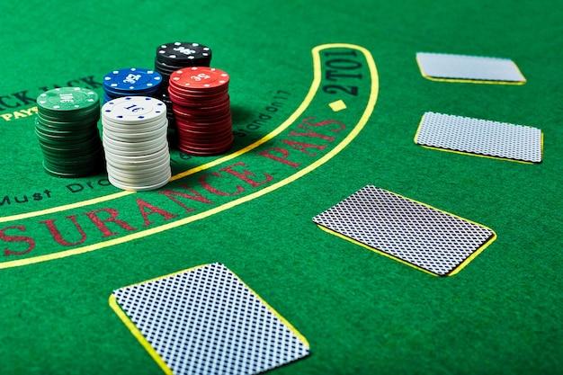 Casinofiches en dek van kaarten die op groene casinotafel liggen, pokerspelconcept