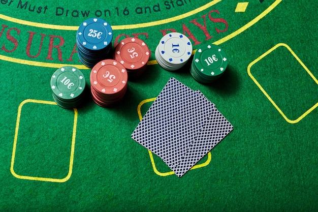 Casinofiches en kaartspel liggend op groene casinotafel, pokerspelconcept, bovenaanzicht.