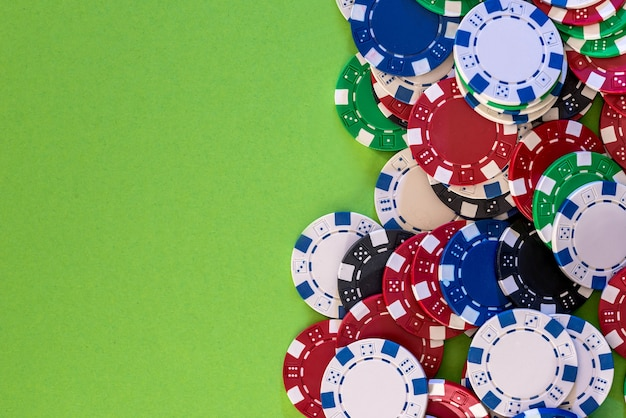 Casinofiches, geïsoleerd op groene achtergrond, close-up.