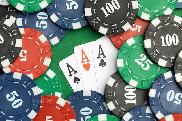 Casinofiches op groene achtergrond met aaskaarten