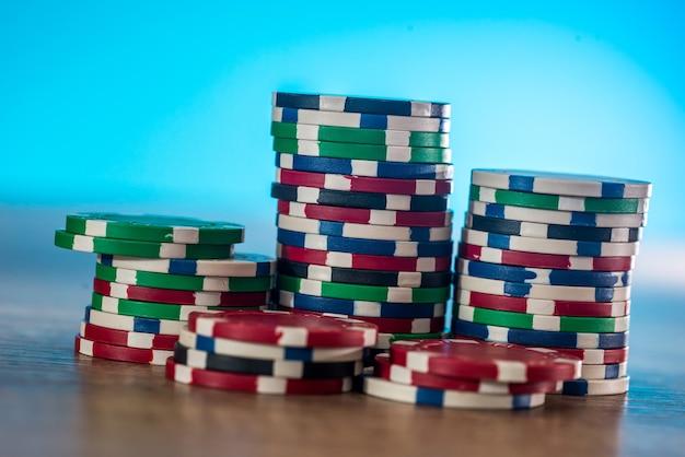 Casinofiches op houten tafel met blauwe achtergrond