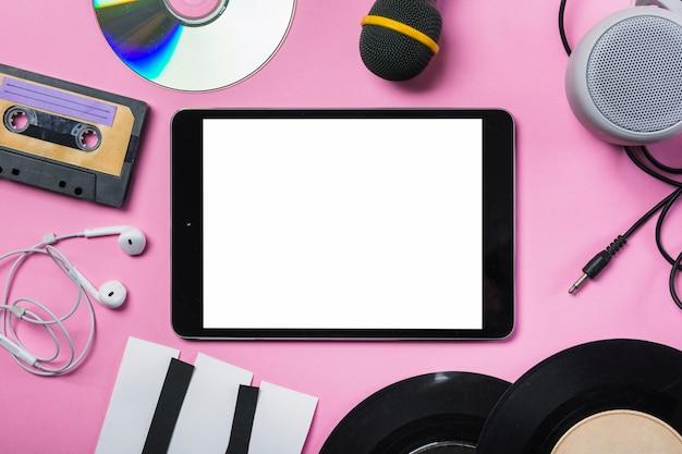 Cassette bandje; cd; oortelefoon; vinylplaat; microfoon; spreker; papieren piano toetsen rond de digitale tablet op roze achtergrond