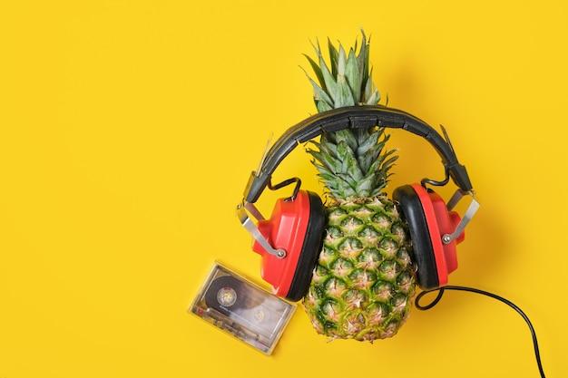 Cassette en ananas in rode retro koptelefoon op gele achtergrond, bovenaanzicht