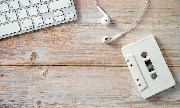 Cassette met koptelefoon met een computertoetsenbord op houten vloertechnologieën voor muziekontwikkeling