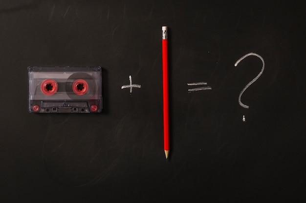 Cassetteband plus rood potlood is gelijk aan vraagteken op zwarte achtergrond