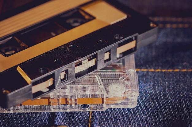 Cassettebandaudio op jeansstof in duisternis.