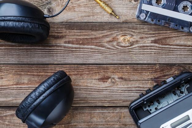 Cassettebandjes, cassettespeler en koptelefoon over houten tafel. bovenaanzicht. retro concept met lege ruimte voor tekst, logo, enz.