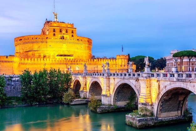 Castel sant'angelo en de sant'angelo-brug tijdens schemeringzonsondergang in rome, italië. Premium Foto