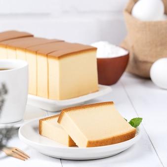 Castella (kasutera) - mooi heerlijk japans gesneden biscuitgebakvoedsel op witte plaat over rustieke witte houten lijst, sluit omhoog, exemplaarruimteontwerpconcept.