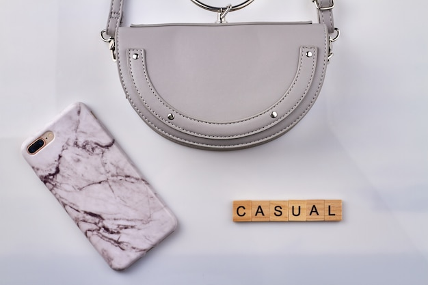 Casual accessoires concept plat leggen. womens handtas en smartphone geïsoleerd op een witte achtergrond.